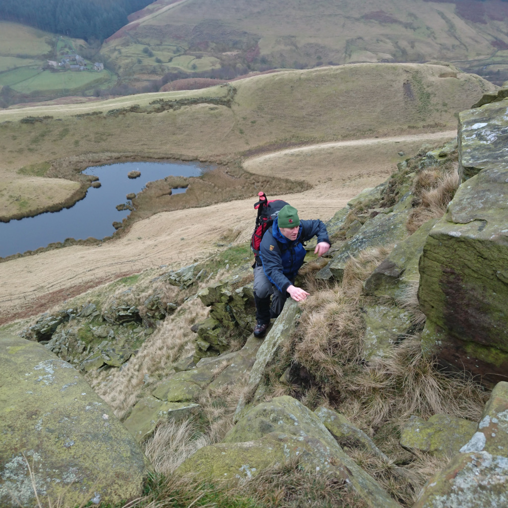Kial scrambling to the top of Alport Castle, Peak District on a autumn day