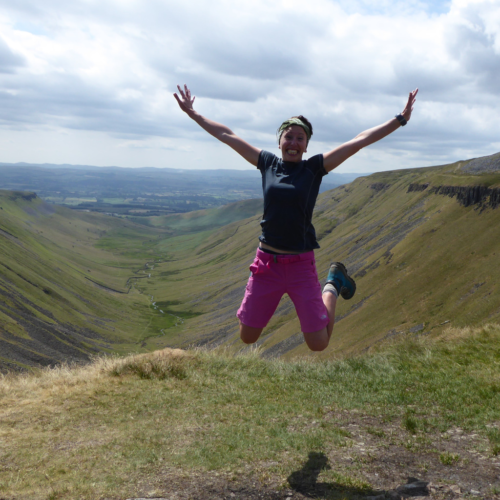 Gemma Scouga jumping for joy at the top of High Cup Nick, North Pennines