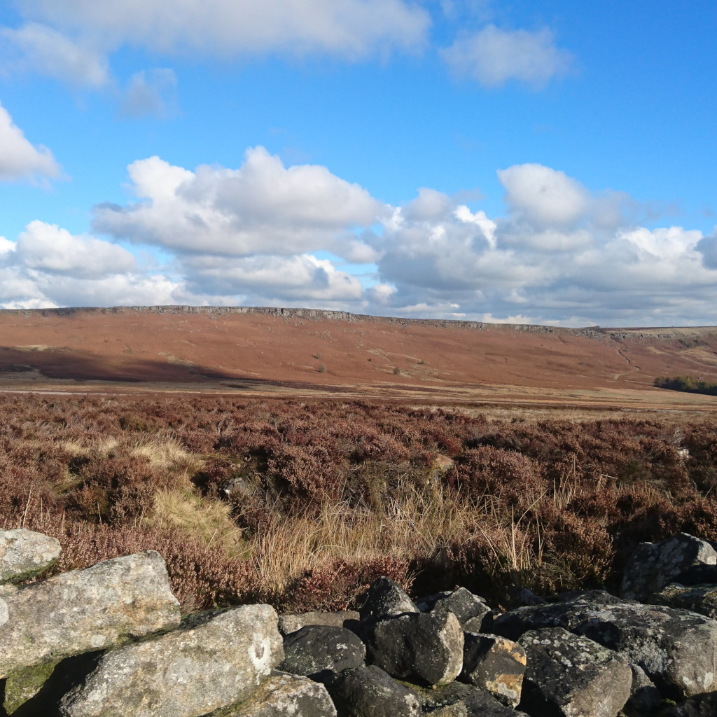 Blue skies and cloud contrast against the heath and moorland landscape of Stanage Moor and Stanage Moor