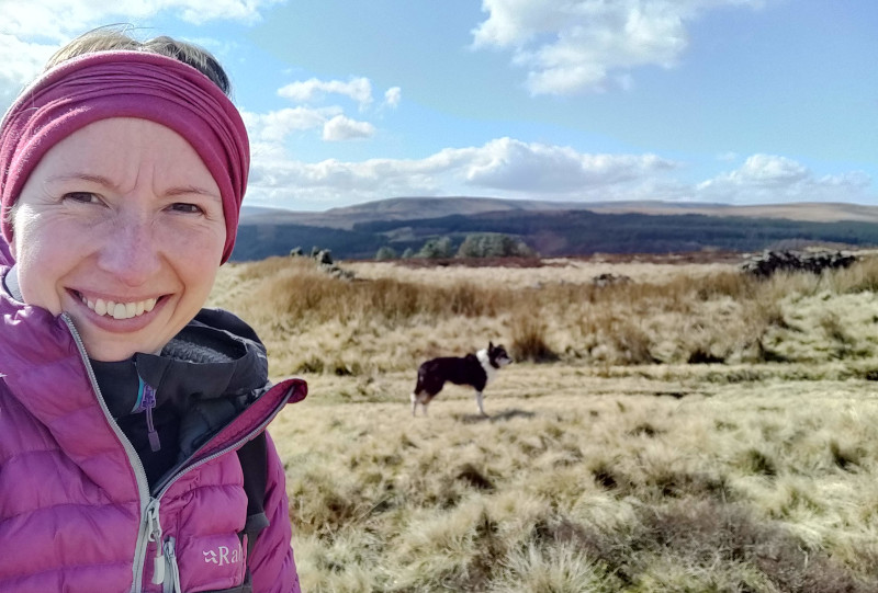 Gemma with down jacket and buff somewhere in the Peak District
