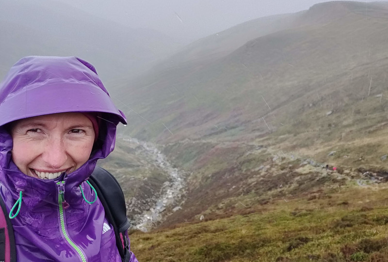 Gemma in torrential rain leading a group of clients up Kinder, Peak District.
